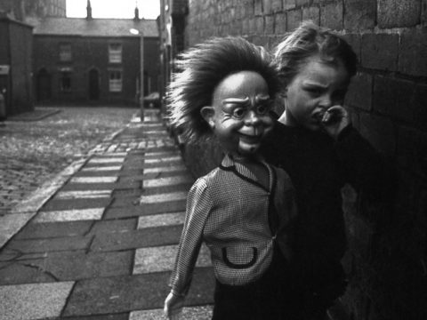 Adrian Turner - The Shot I Never Forgot - girl carries doll through the streets of Oldham in 1970