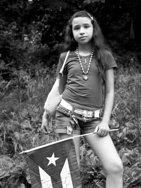Erica McDonald - The Shot I Never Forgot - Portrait of a girl holding flag during Puerto Rican Day Parade in New York