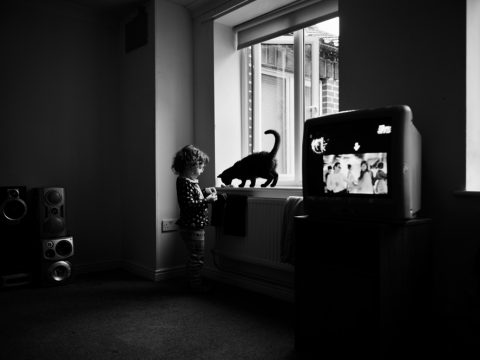 JIm Mortram - The Shot I Never Forgot - Black and white image of girl playing with cat on window sill whilst TV plays