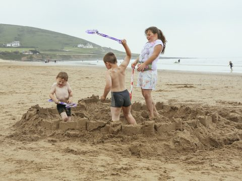 Kevin Meredith - The Shot I Never Forgot - Three children on beach destroying a sandcastle