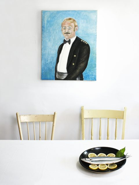 Kyoko Hamada - The Shot I Never Forgot - A plate with two Mackerels sits on a table under a portrait painting of a man in formal suit