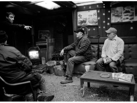 Simon Carruthers - The Shot I Never Forgot - four men chat in roadside lay-by cafe