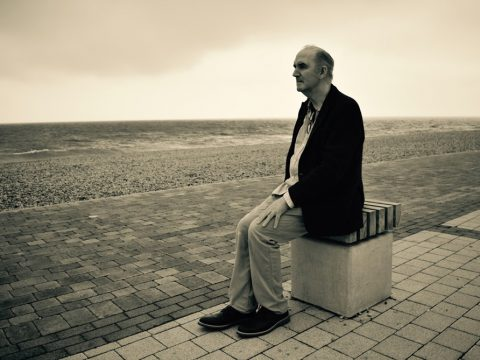 Stuart Pilkington - The Shot I Never Forgot - portrait of Tim Andrews sitting on the promenade in Brighton