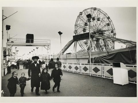 Alys Tomlinson - The Shot I Never Forgot - 'The Family, Coney Island 1998' Black and white photograph of a family walking past ferris wheel in Coney Island